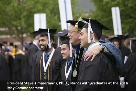 President Steve Timmermans, Ph.D., stands with graduates at the 2014 May Commencement