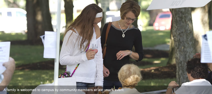 A family is welcomed to campus by community members at last year's event.