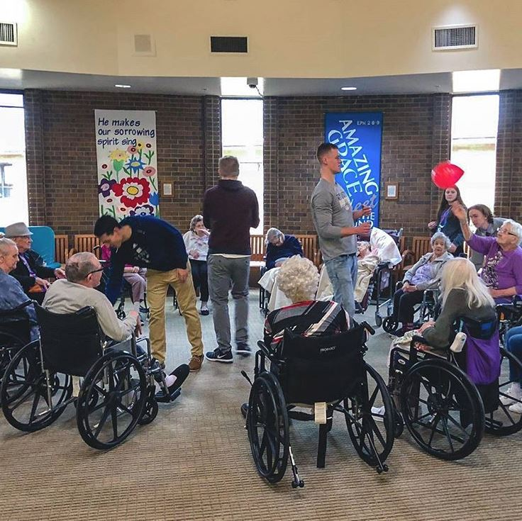 Students helping wheelchair bound seniors for PERK outing
